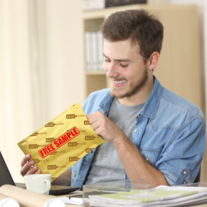 Business man smiling at table opening package labeled sample